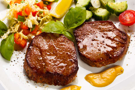 Top view close-up grilled steaks and vegetable salad photo