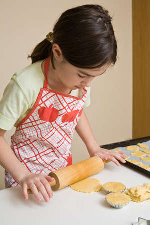 little dough: Young girl rolling dough to bake cookies Stock Photo