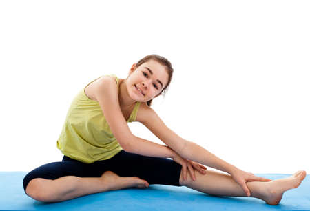 Girl sitting and stretching on yoga mat photo