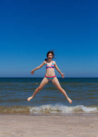 one teenager: Girl jumping in beach