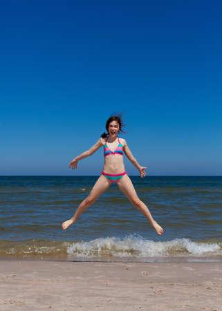 teen girl bikini: Girl jumping in beach