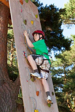 niño trepando: Chico escalada en el parque de aventuras