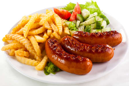 grilled sausages: Grilled sausages with chips and vegetables Stock Photo
