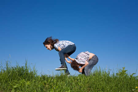bouncing: Girl jumping over boy in meadow