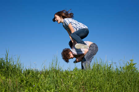 dynamic activity: Girl jumping over boy in meadow