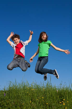 bouncing: Girl and boy jumping in meadow
