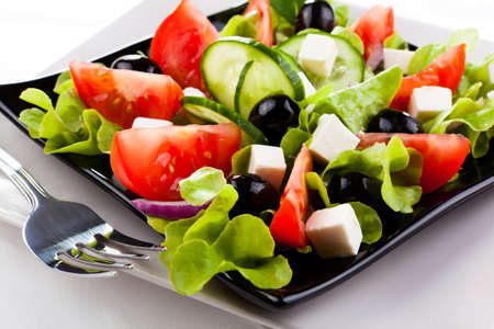 lowfat: Vegetable salad with cheese on black plate