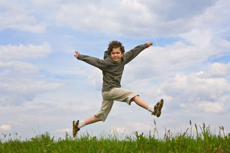dynamic activity: Boy jumping in meadow