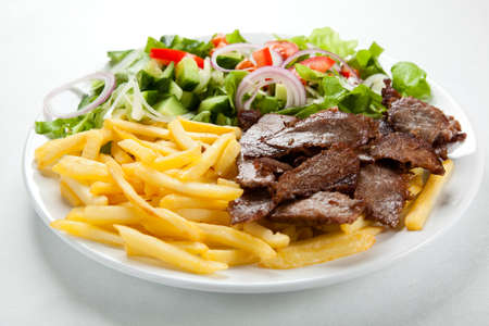 gyros: Grilled meat with French fries and vegetable salad Stock Photo