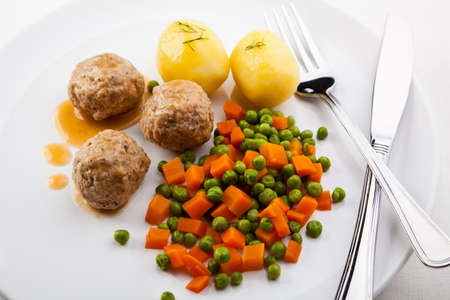 Meatballs with peas, carrot and potatoes photo