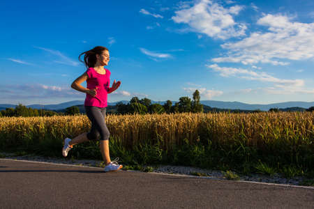sports track: Girl running outdoors Stock Photo