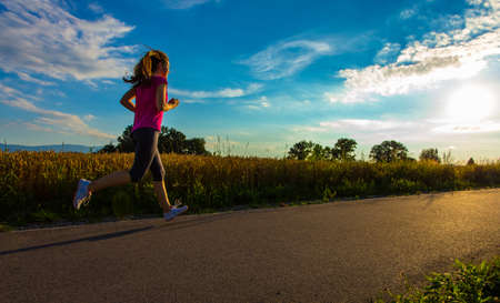 jogging track: Girl running outdoors Stock Photo