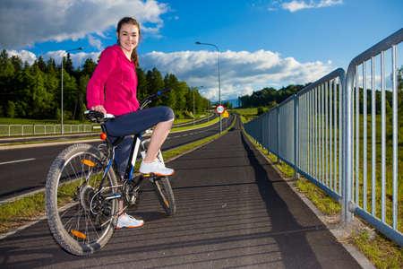 single lane road: Girl riding a bike on cycle lane