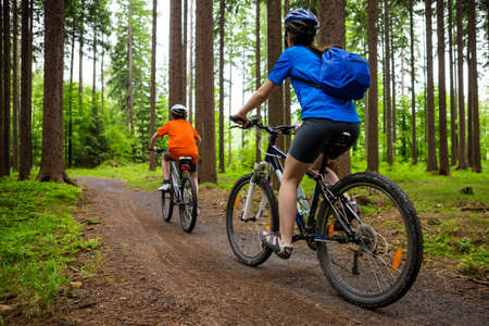Girl and boy riding a bicycle on forest trails photo