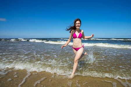personas banandose: Adolescente que juega en la playa