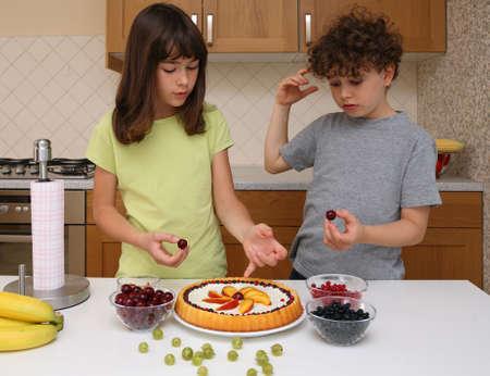 decoracion de pasteles: Cabritos que preparan la torta de la fruta Foto de archivo