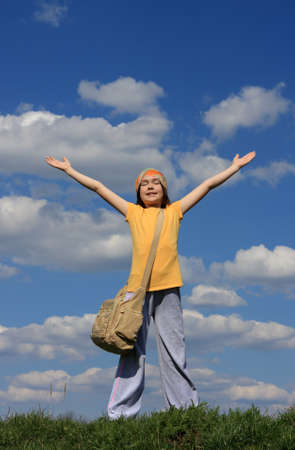 Girl holding arms up in praise against blue sky photo