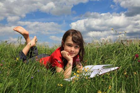 girl reading book: Girl reading book in green meadow
