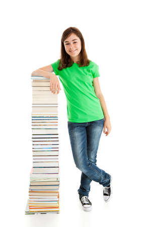 Girl standing beside pile of books on white background photo