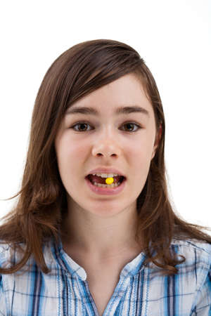 female tongue: Close up of girl biting on a pill Stock Photo