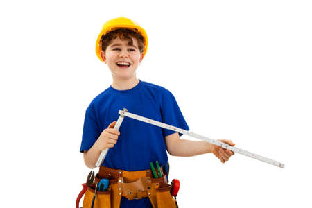 10 to 12 years: Boy as a construction worker holding a yardstick
