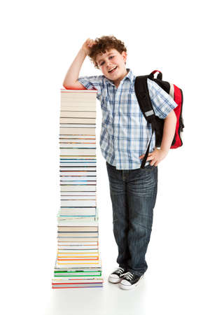 Boy standing beside pile of books with his schoolbag photo