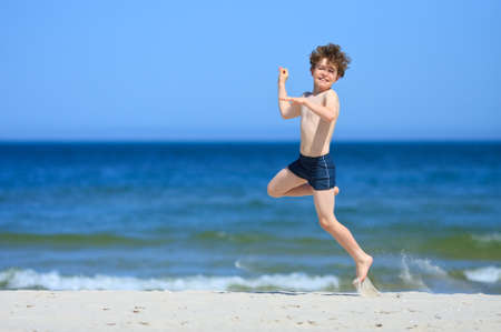 10 to 12 years old: Side view of boy having fun on the beach Stock Photo