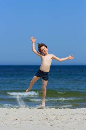 10 to 12 years: Boy having fun on the beach