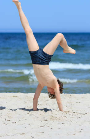 10 to 12 years old: Close up of boy having fun on the beach Stock Photo