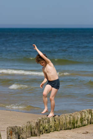 10 to 12 years old: Boy walking on rocks beside the the beach Stock Photo