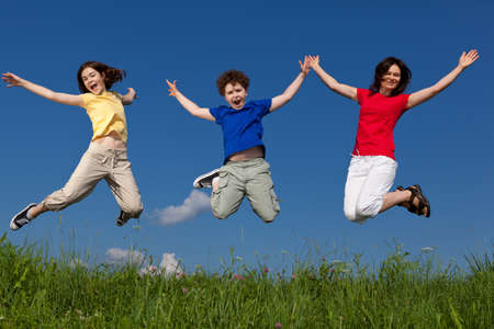 hopping: Mother and children jumping outdoors Stock Photo