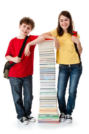 Boy and girl standing beside pile of books on white background photo