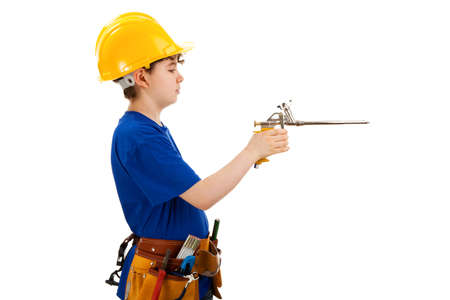 10 to 12 years old: Boy as a construction worker holding an air blow gun Stock Photo