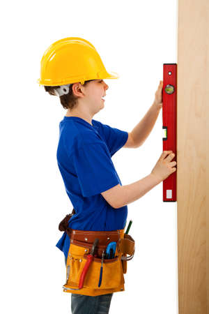 10 to 12 years old: Boy as a construction worker holding a measuring tape Stock Photo