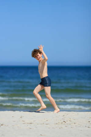 10 to 12 years: Side view of boy having fun on the beach Stock Photo