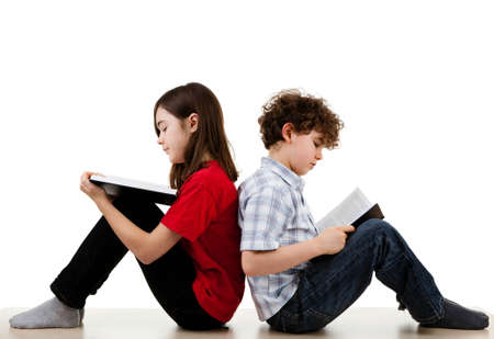 old people reading: Boy and girl reading book while leaning on each other Stock Photo