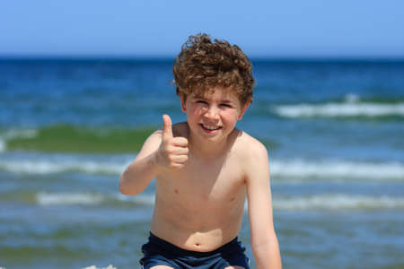 10 to 12 years old: Close up of boy having fun on the beach and showing thumbs up