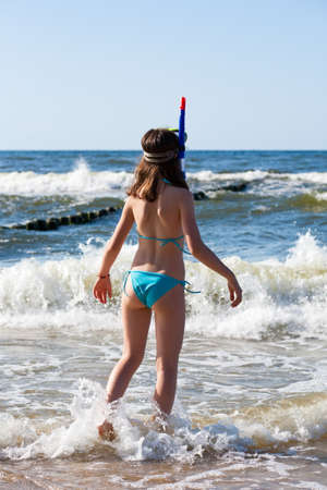 Back view of girl having fun on the beach with snorkeling equipment photo