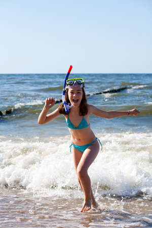 Girl having fun on the beach with snorkeling equipment photo