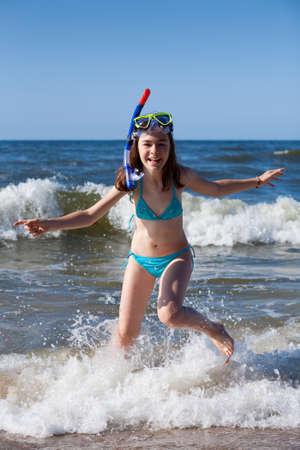 Fille de s'amuser sur la plage avec un équipement de plongée en apnée
