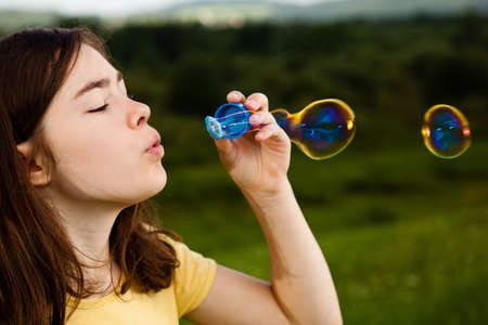 Close up of girl blowing soap bubbles photo