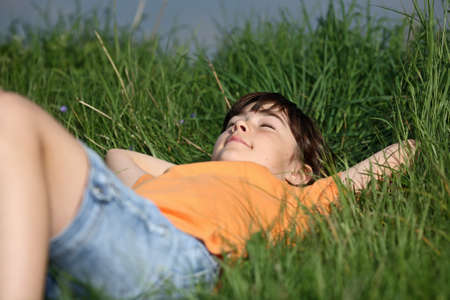 one eye closed: Girl lying on the field with eyes closed