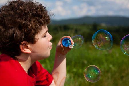 Close up of boy blowing soap bubbles photo