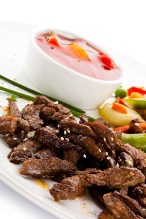 Close up of cooked meat with vegetables and sauce photo