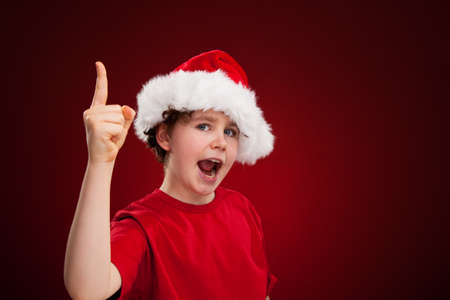 christmas costume: Boy with Santa Claus Hat with finger pointing up