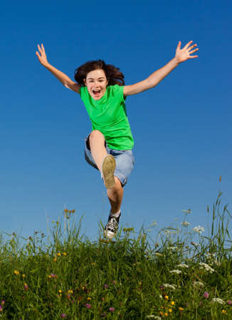 girl action: Girl jumping outdoors against blue sky