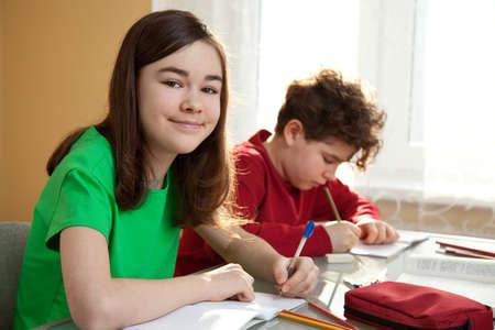 niños escribiendo: Niño y niña aprendizaje en casa Foto de archivo