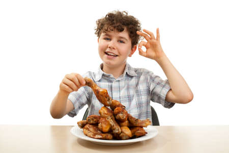 chicken leg: Kid eating chicken drumsticks isolated on white