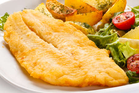 trout: Fried fish fillet with baked potatoes and vegetables