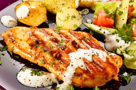 Grilled chicken fillet, baked potatoes and vegetables photo